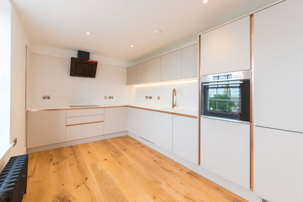 kitchen with wooden flooring, white appliances and cast iron radiator