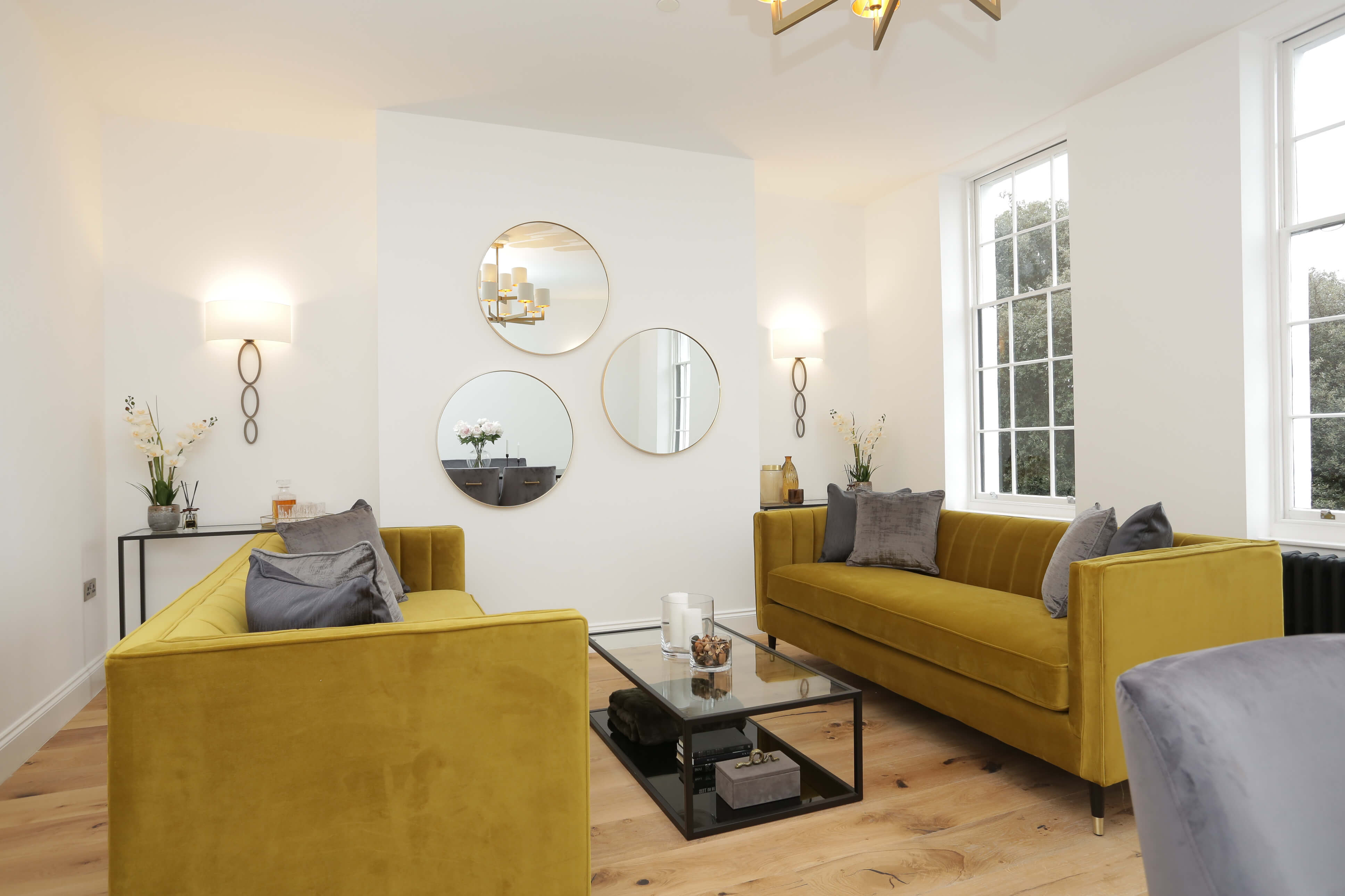 wide angle of contemporary living room with sofa seating, light fittings and mirrors