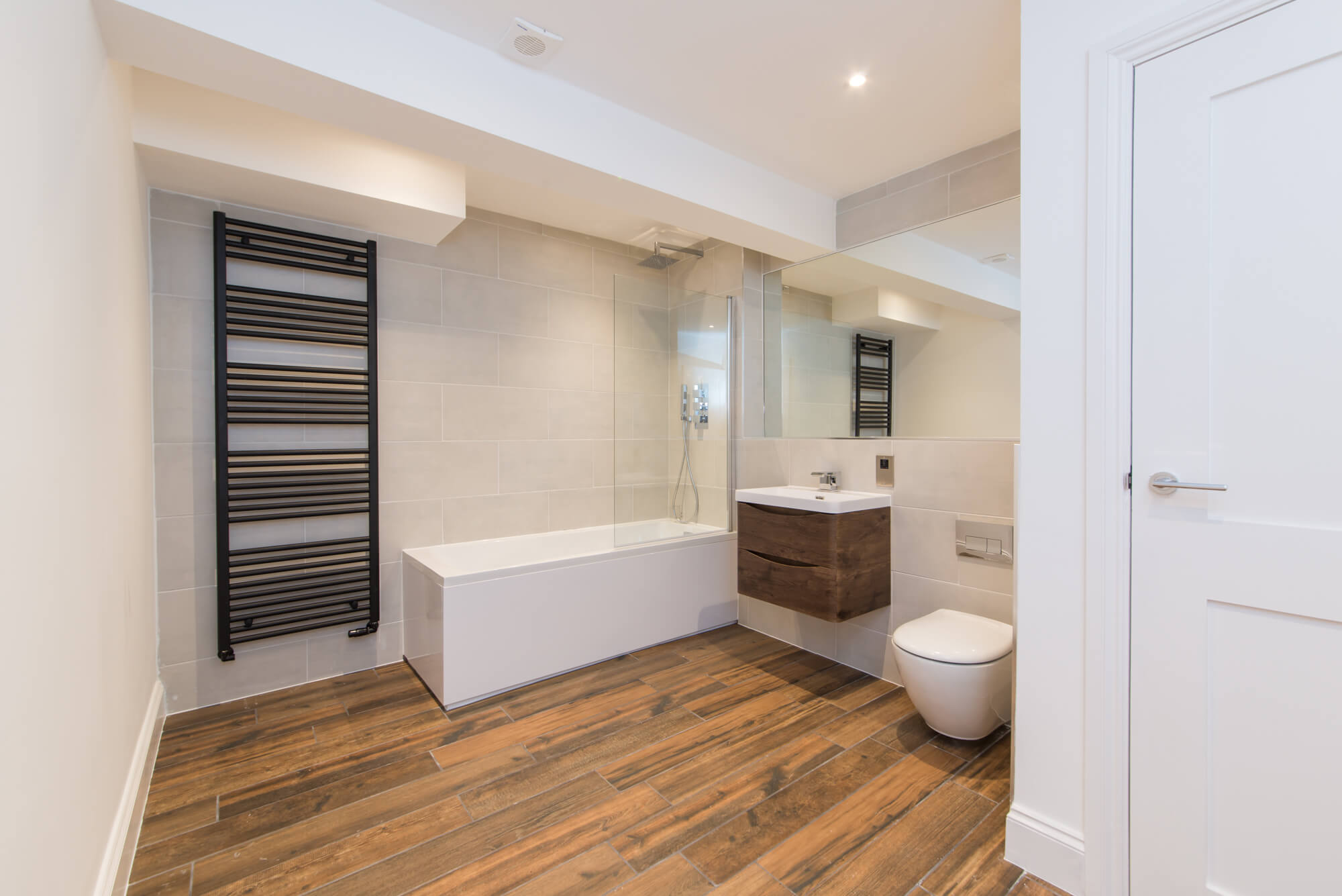 contemproary, spacious bathroom with heated towel rail and wall hung toilet