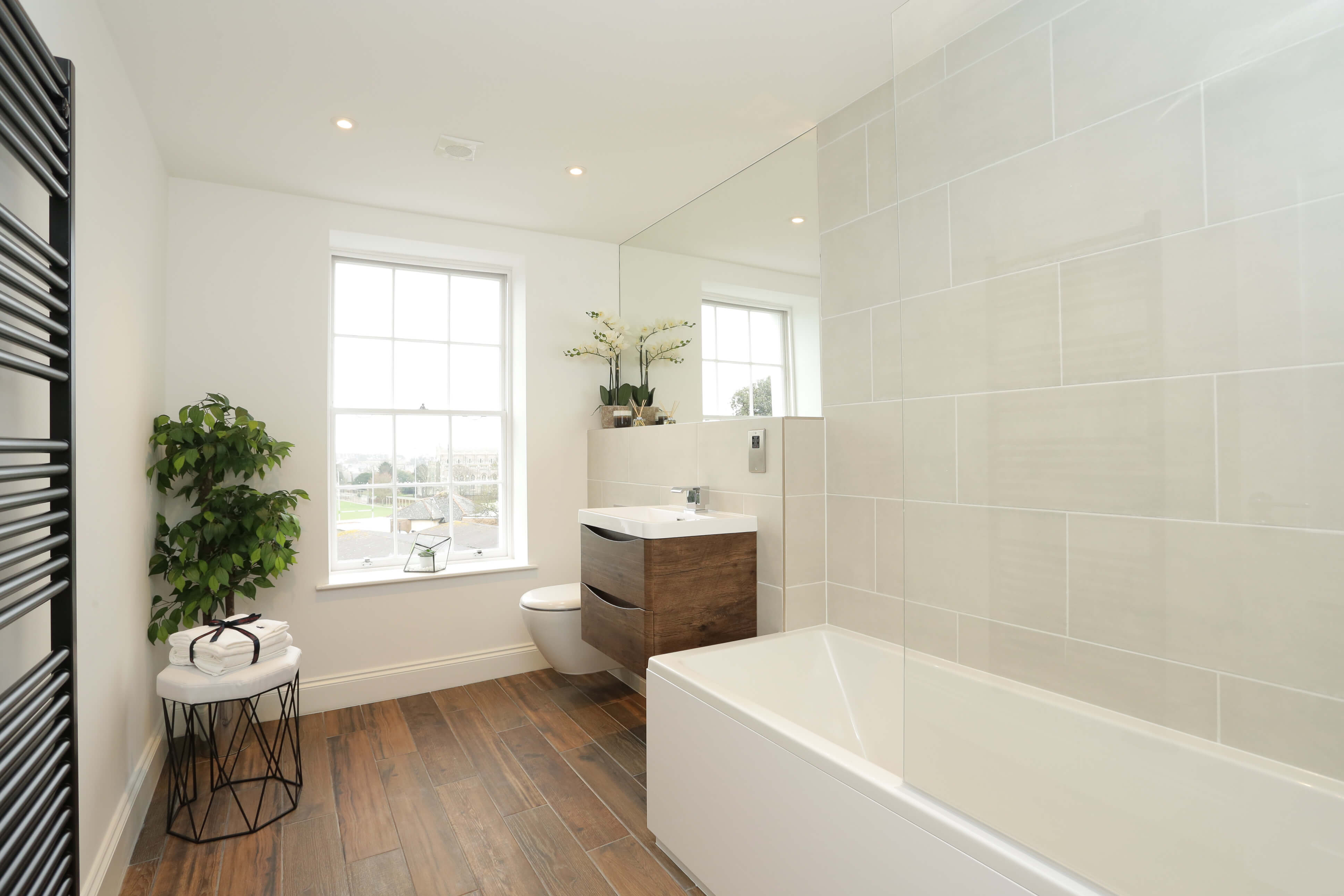 bathroom with large fitted wall mirror, bath and wall hung concealed toilet