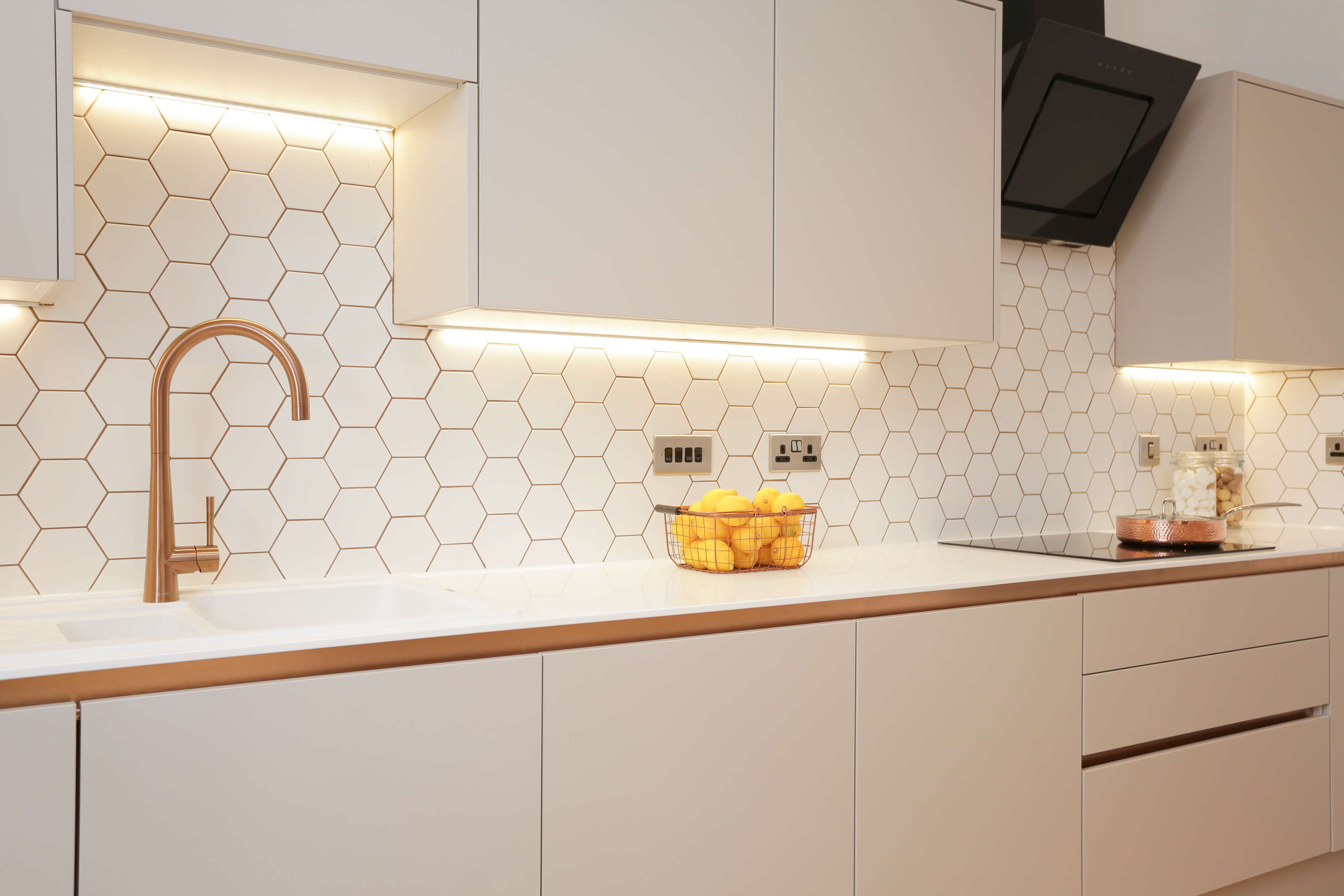 close up of kitchen with hexagonal splashback tiles and stylish copper accents and taps