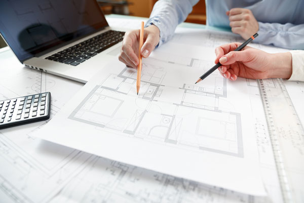 Two people working on floor plans
